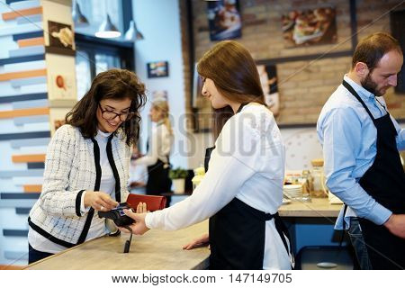 Female guest paying by credit card in cafeteria.