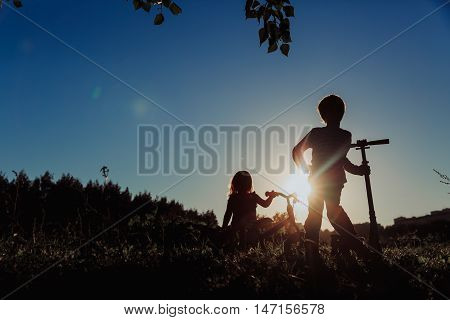 kids riding bike and scooter at sunset, active sport family