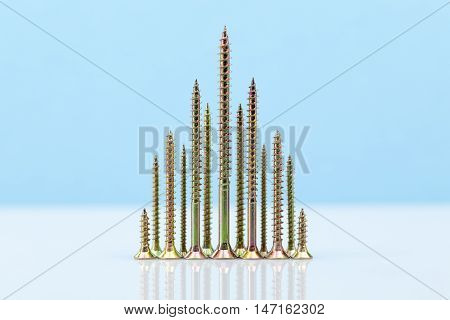 Screw-shaped  metal tree on light blue and white background
