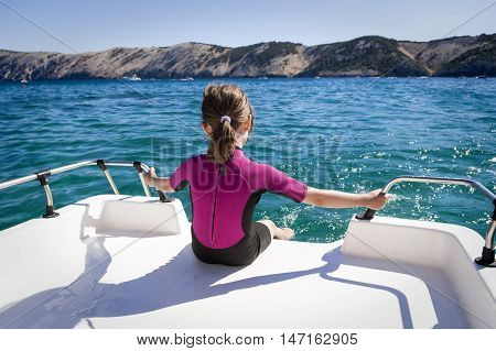Little girl sitting at the back of the boat cooling legs in water. Croatia rab island.