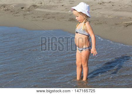 little girl sits at the water's edge