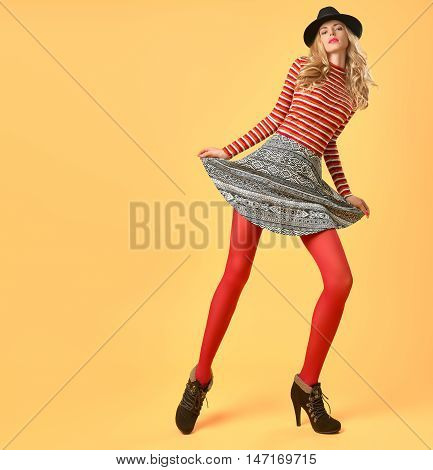 Fall Fashion. Model Woman in Autumn Fashion Outfit Having Fun. Stylish Sweater Trendy Hat in red fashion pantyhose. Glamour Playful Blonde Sexy girl Long Legs. Fashion Pose.Makeup.Fall Autumn.Creative