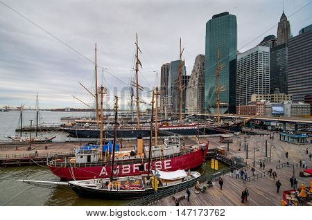 New York City USA - November 15 2011: People walk in Landmark seaport located next to Wall Street and financial center in nasty weather at November 15 2011 NYC. The port is a designated historic district containing the largest concentration of 19th centur