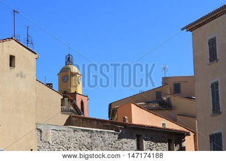 Belltower Of Saint Tropez Among Traditional Provencal Buildings With Blue Sky