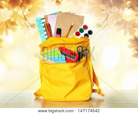 Yellow backpack with school supplies on wooden table against blurred autumn leaves background. School concept.