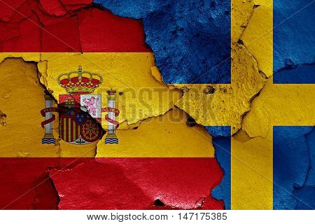 flags of Spain and Sweden painted on cracked wall