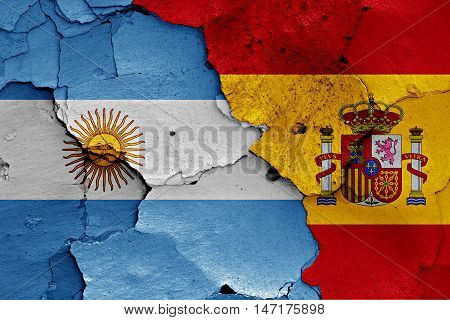 flags of Argentina and Spain painted on cracked wall