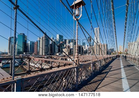 New York USA - November 18 2011: People cross the Brooklyn bridge in New York City at November 18 2011. This is the famous bridge built in the 1860s with its stone gothic arches connecting Brooklyn and Manhattan. It has an upper level for cyclists and ped