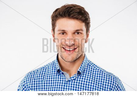 Portrait of cheerful attractive young man in checkered shirt over white background