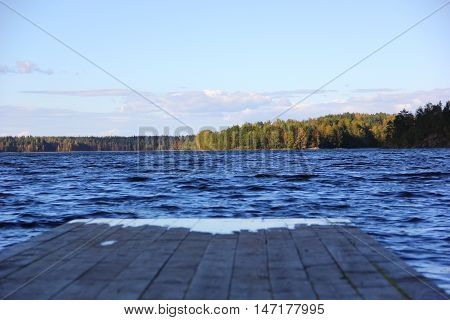 At the end of the wooden pier, soaked in water, wet and dark-blue waters of the lake, the rippling water, on the horizon, an island with a forest, the sky with gentle clouds