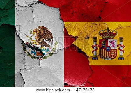 flags of Mexico and Spain painted on cracked wall