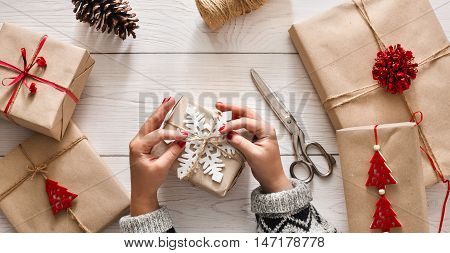 Woman's hands wrapping christmas holiday handmade present in craft paper with twine ribbon. Making bow at xmas gift box, decorated with snowflake. Scissors on white wooden table, top view.