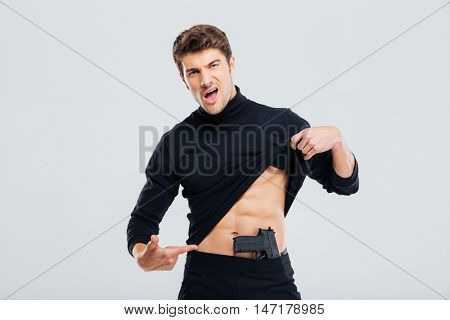 Confident young man posing and poiting on his gun