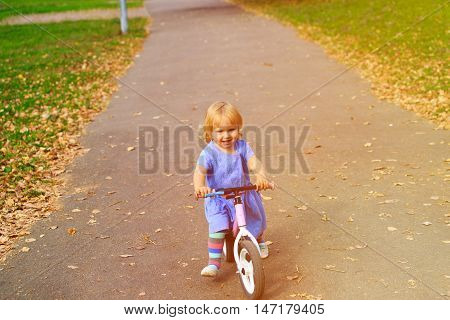 cute little girl riding runbike in autumn, active kids sport