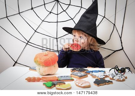 little girl eating cookies on halloween, kids trick or treating