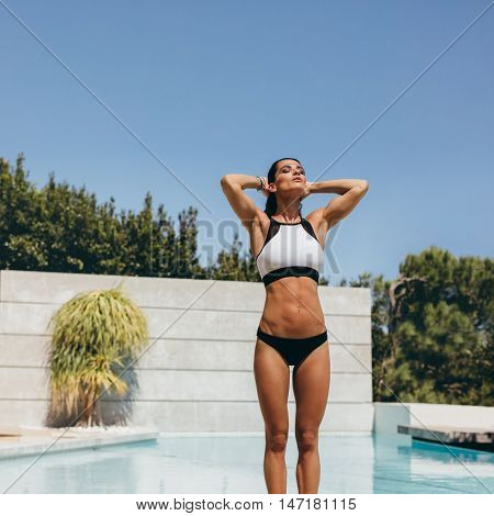 Young Woman Standing By Swimming Pool After A Swim