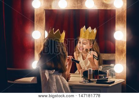 Cute little actress. Child girl in Princess costume on the background of theatrical scenes and mirrors.