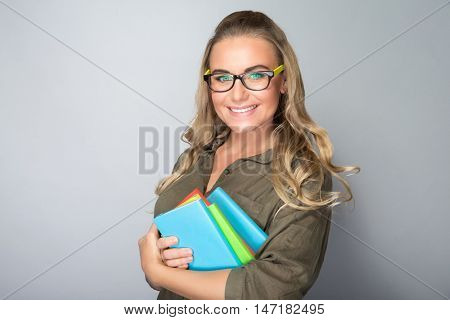 Portrait of a happy smiling student girl with colorful books in hands over gray background, enjoying education in high school