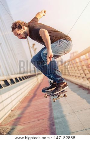 Skateboarder Skates And Doing Jumps Over A City Bridge. Free Ride Street Skateboarding