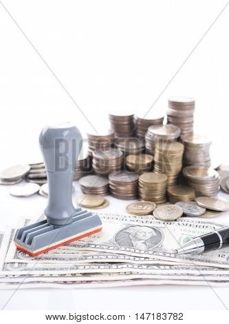 Rubber stamper pen and pile coin money with dollar bills concept success finance and banking