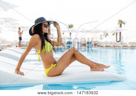 Portrait of a pretty young woman sitting on deckchair outdoors at the swimming pool