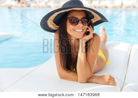Portrait of a happy cute woman talking on the phone on deckchair outdoors