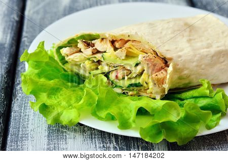 Healthy homemade shawarma on a white plate with lettuce. Healthy eating