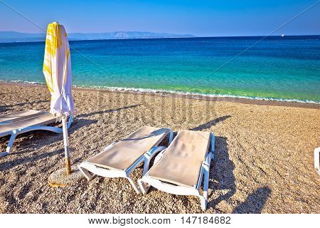Idyllic turquoise beach parasol and deck chair Zlatni Rat Bol Croatia