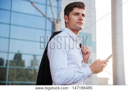 Pensive young businessman holding mobile phone standing with jacket over shoulder outdoors