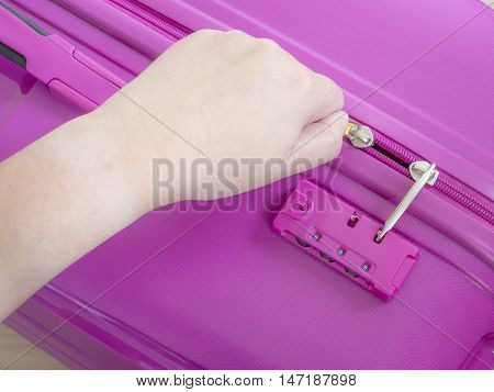 Woman use left hand to close zipper on pink suitcase