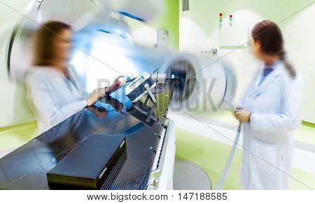 Two blurred doctor figures in a hospital room with hi-tech x-ray magnetic resonance scanner equipment
