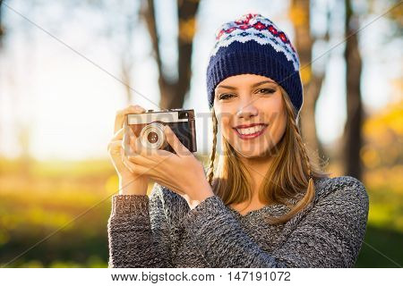 Modern young female photographer with film camera in autumn. Closeup portrait of beautiful happy young woman with analogue camera in park in fall. Retouched, vibrant colors.