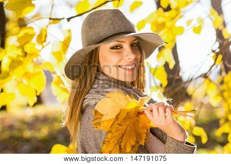 Beautiful young woman in park in autumn holding leaves. Closeup outdoor portrait of happy cheerful young Caucasian woman in gray sweater, floppy hat and scarf posing. Vibrant colors, natural light.