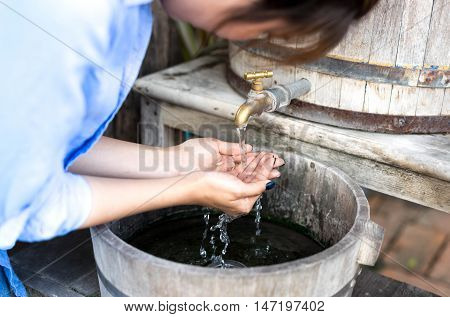 Woman washing her hand under running water with golden tap