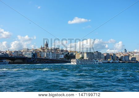 Istanbul Turkey - July 5 2016 : Locals are fishing on the Galata Bridge while tourists are going for a cruise on the Bosphorus on one of the many ships. In the background New Istanbul with the Galata Tower.