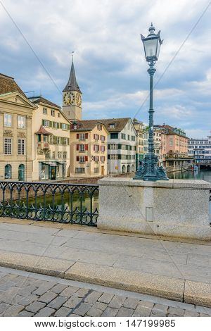 Beautiful view of historic city center of Zurich with famous Fraumunster Church and Munsterbucke crossing river Limmat on a sunny day with blue sky and clouds in summer, Canton of Zurich, Switzerland