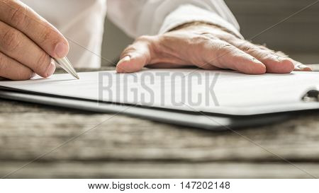 Man in white shirt signing business document or subscription form with silver pen on wooden desk. Low angle view.