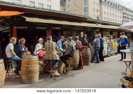 VIENNA, AUSTRIA - JUN 6, 2013: People in outdoor cafe in area of Naschmarkt most popular market of the city on June 6, 2013. Food and drinks from 1793
