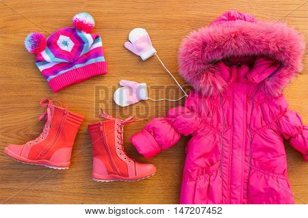 Children's winter clothes: warm pink jacket, hat, mittens, boots. Top view.