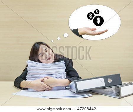 Closeup happy working woman sleeping with happy face after she finish her work and good dream to receive money with work paper in front of her on blurred wood desk and wall textured background in room