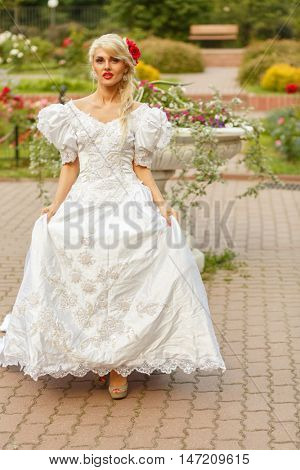 Full portrait of beautiful woman in white long dress with roses in her hair walking in summer park