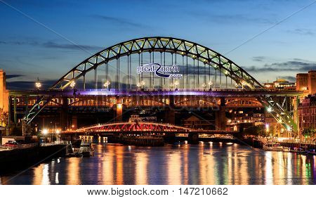 Newcastle and Gateshead at sundown showing Gateshead Millennium Bridge sage and Tyne Bridges.