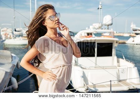 Young beautiful brunette girl in suglasses standing at the sea pier