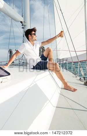 Handsome young confident man drinking beer while resting on the yacht