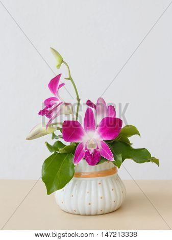 Boquet of orchid flowers and green leaf on arranged table