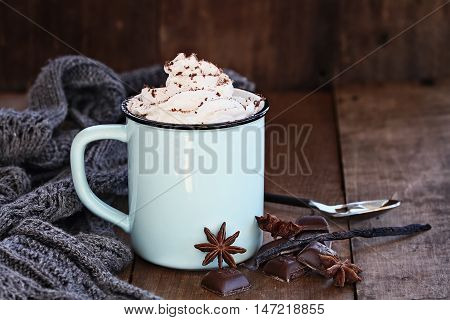 Enamel cup of hot cocoa or coffee for Christmas with whipped cream shaved chocolate vanilla pod spices and gray scarf against a rustic background. Shallow depth of field with selective focus on drink.