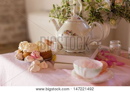 Morning tearoom table setting with flower composition and cakes