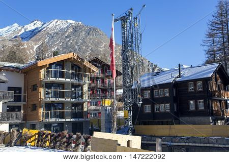 SWITZERLAND, SAAS-FEE, DECEMBER, 27, 2015 - Building of new chalets near the mountains over 4,000 meters high on the charming Swiss resort of Saas-Fee, Switzerland