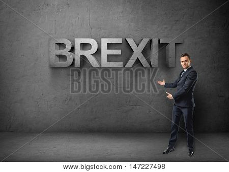 Businessman stands showing big 3d 'brexit' word by both hands on concrete background. British withdrawal. Euroscepticism. Unired Kingdom and European Union.