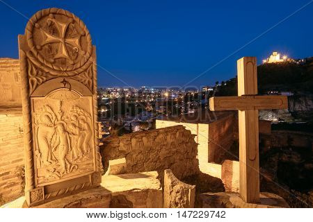 The Orthodox Icon And Wooden Cross On The Area Of Ancient Fortress Narikala. View Of Evening City And Tabor Monastery Of The Transfiguration On Taboris Mta Or Tabor , Favor, Mount, Tbilisi, Georgia.